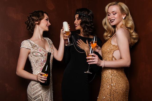 Tři ženy ve společenských šatech, připíjející si šampaňským.jpg